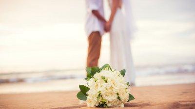 Buquê de flores no chão da praia, ao fundo, desfocado, há um casal de noivos vestidos de branco