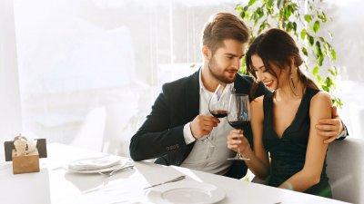 Casal em restaurante, conversando e bebendo vinho.