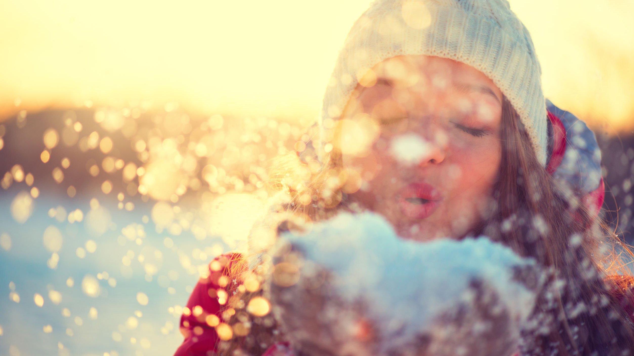 Foto de mulher assoprando neve