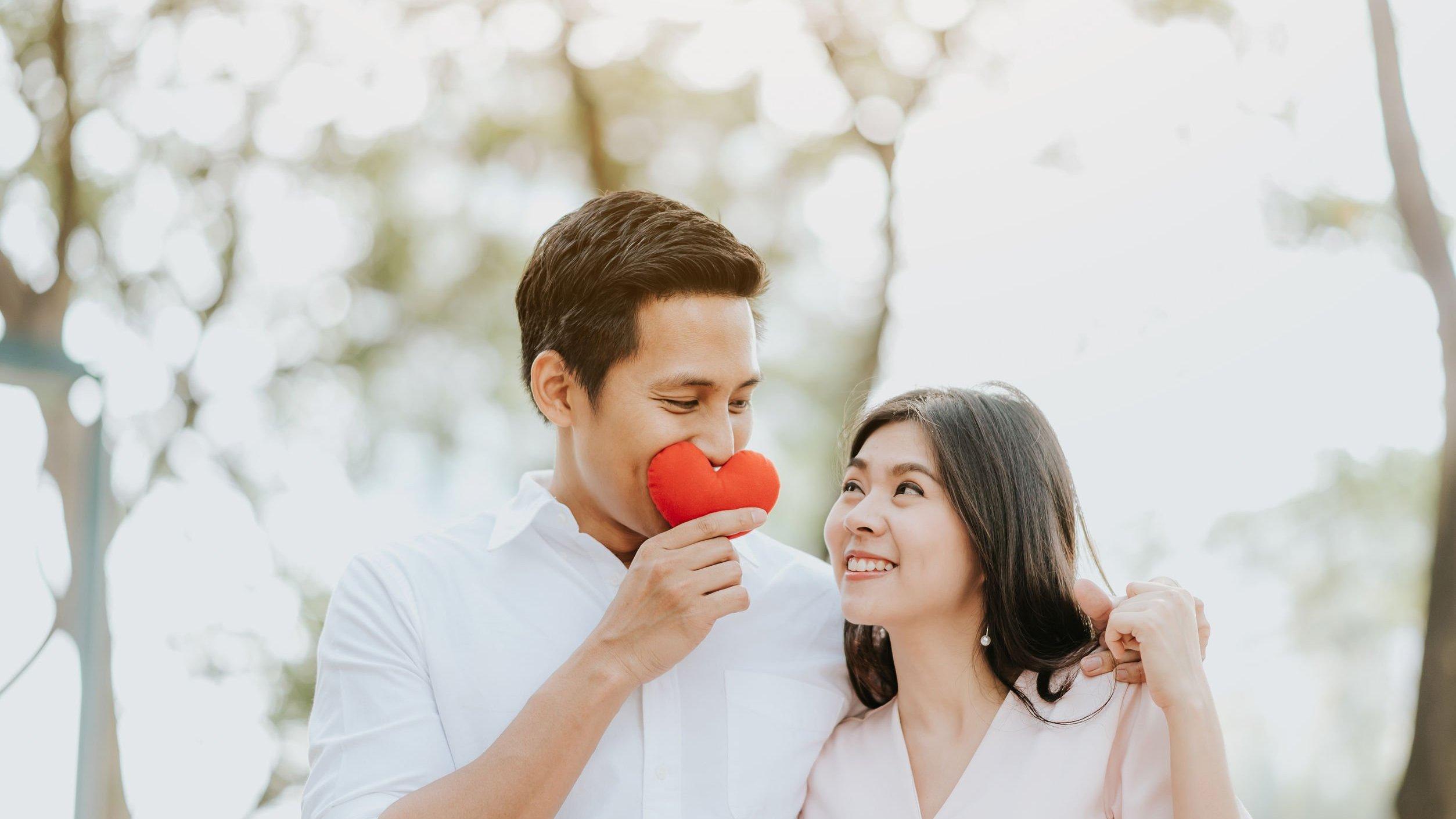 Homem segurando um coração de pelúcia e olhando para a namorada