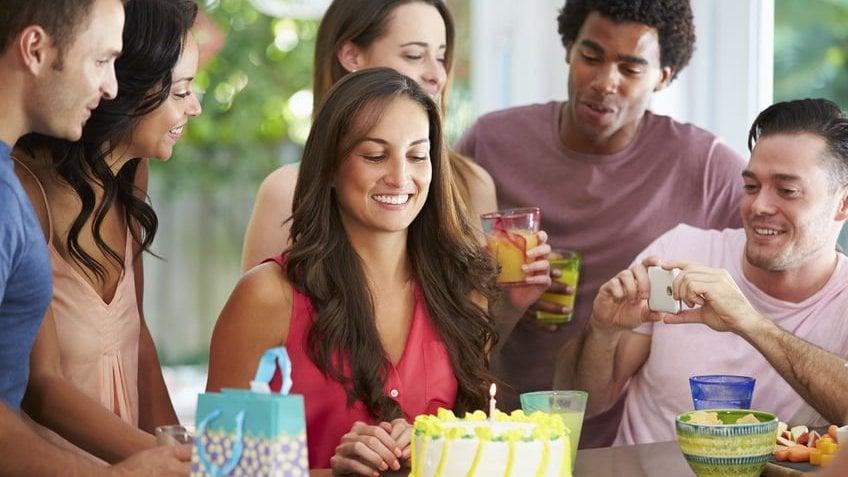 Mulher celebrando aniversário em casa com amigos em volta