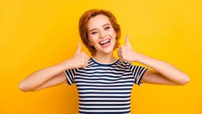 Menina com polegares erguidos e sorrindo