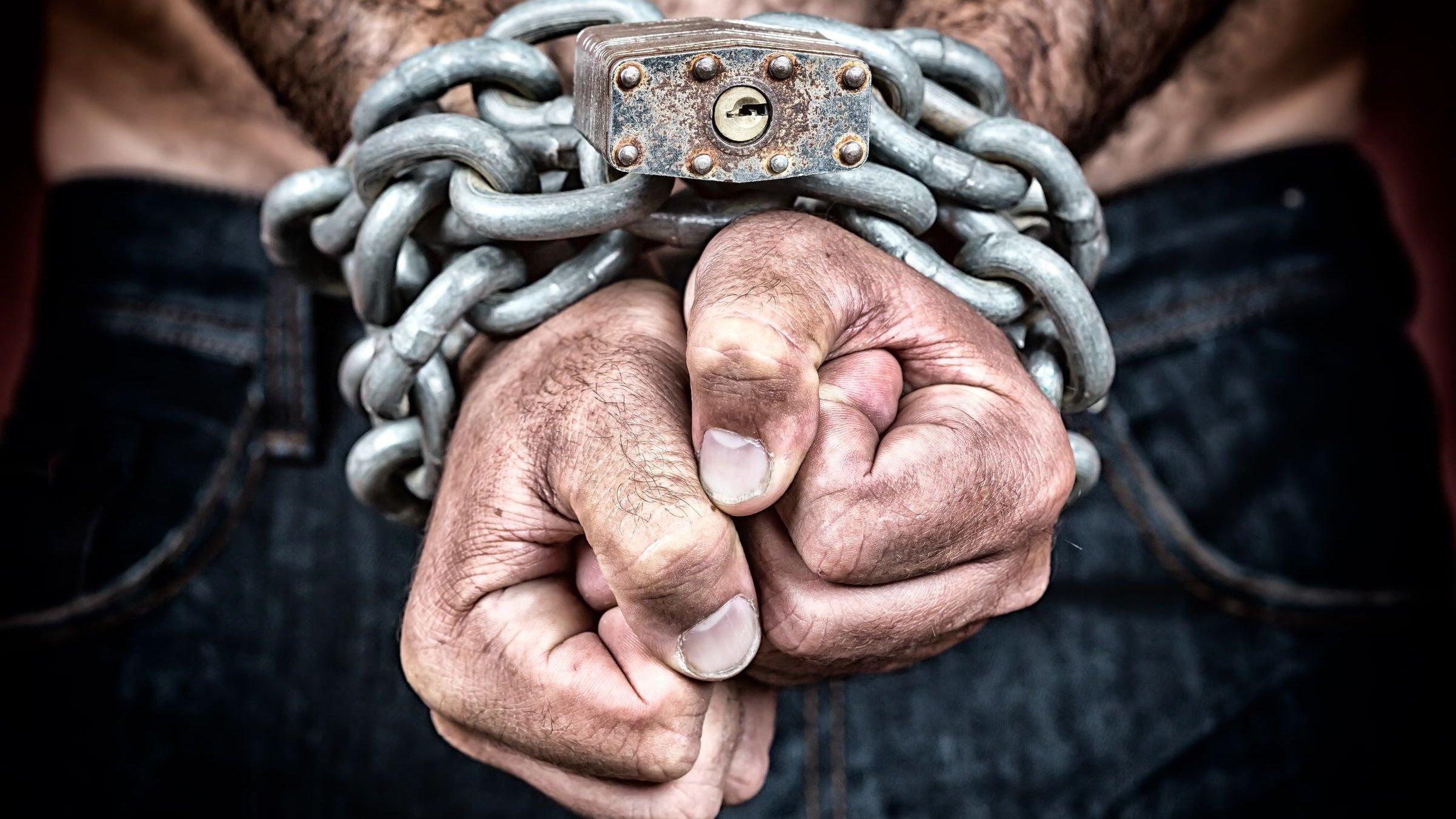 Homem com os pulsos presos por uma corrente e um cadeado. Suas mãos e seus braços estão sujos.
