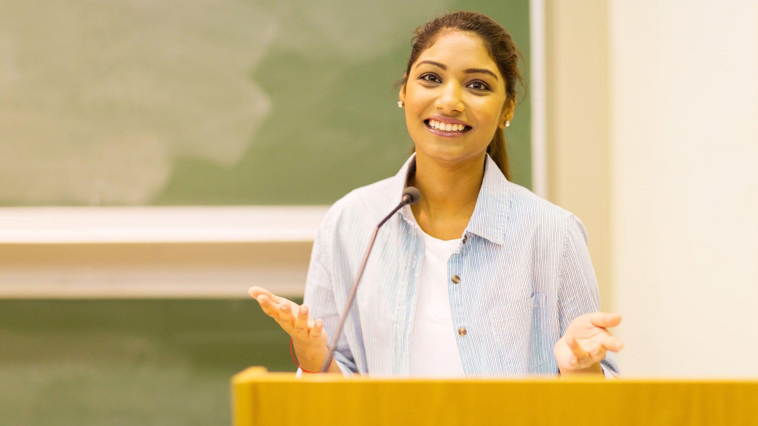 Mulher estudante discursando em sala de aula.