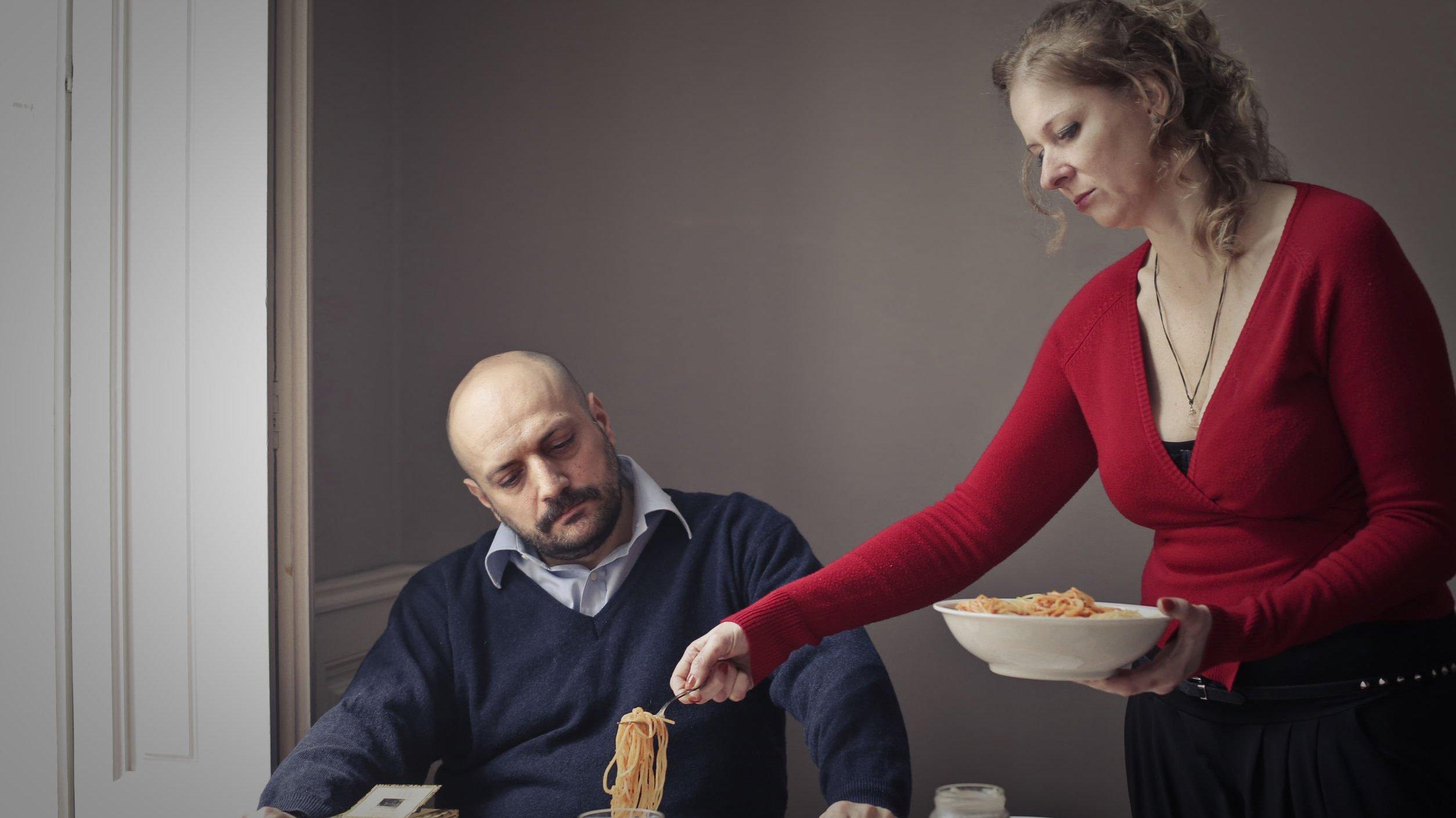 Homem sentado em mesa de jantar com mulher lhe servindo uma porção de macarrão. O homem parece impaciente e a mulher tem uma expressão cansada.
