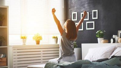 Mulher sentada na beirada da cama de frente para uma janela, com os braços esticados para cima. Pela janela, a luz do sol entra no ambiente.