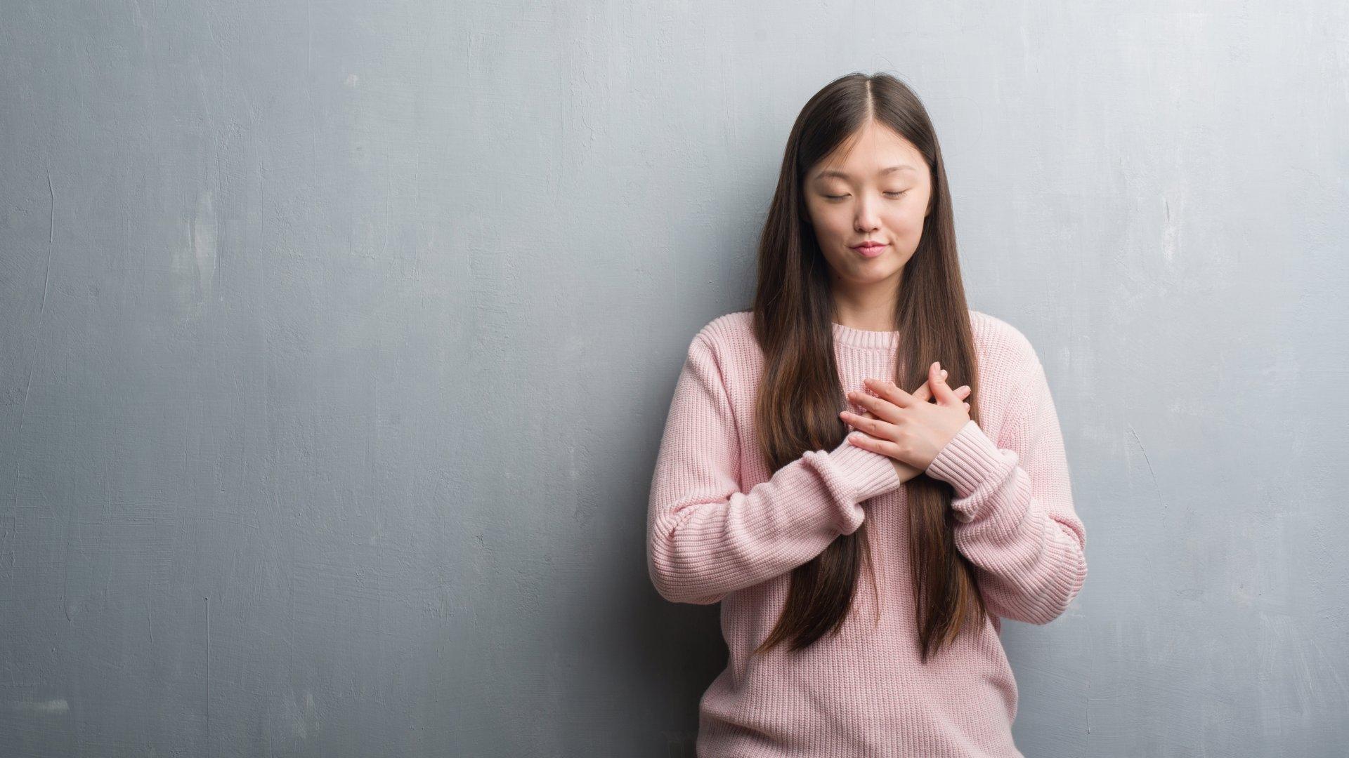 mulher de mãos juntas sobre o coração e de olhos fechados, em sinal de gratidão