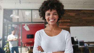 Foto de mulher negra de braços cruzados sorrindo