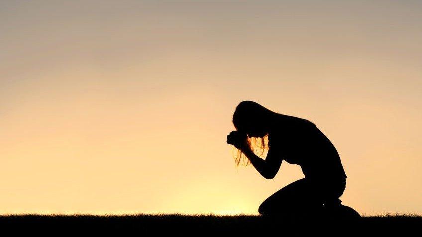 Silhueta e mulher cristã orando em campo