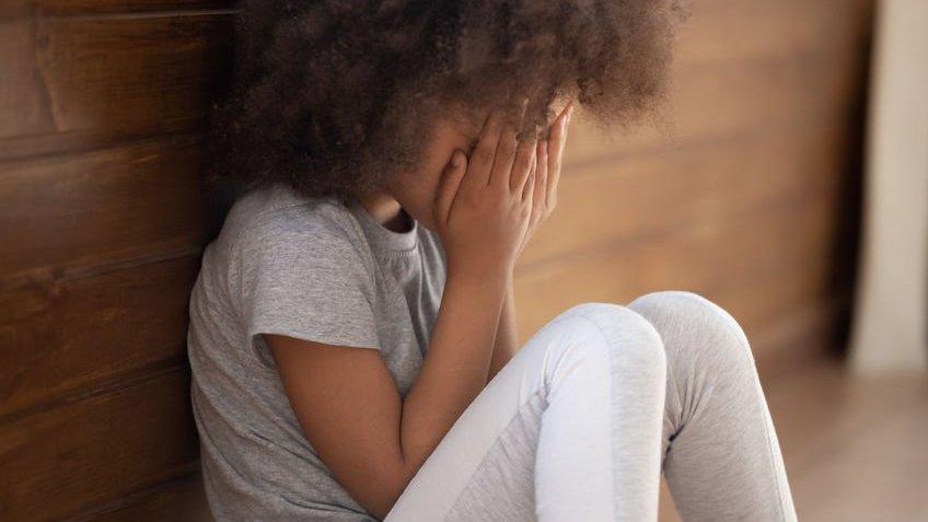 Menina pequena criança chateada, cobrindo o rosto com as mãos, sentada sozinha no chão