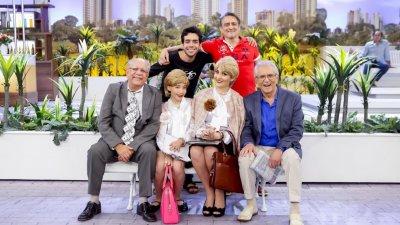 Foto de personagens do programa - A praça é nossa sentados em banco posando para foto