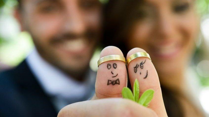 Dedos com rostos de casal e alianças no topo