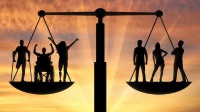 Uma balança com os dois lados equilibrados. Do lado direito, dois homens e uma mulher em pé. Do lado esquerdo um homem sem uma perna com muletas, um homem em uma cadeira de rodas e uma mulher com uma perna mecânica.