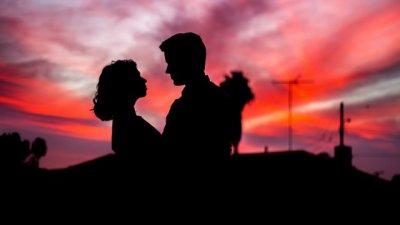 Foto de mulher abraçando homem por trás em um dia ensolarado