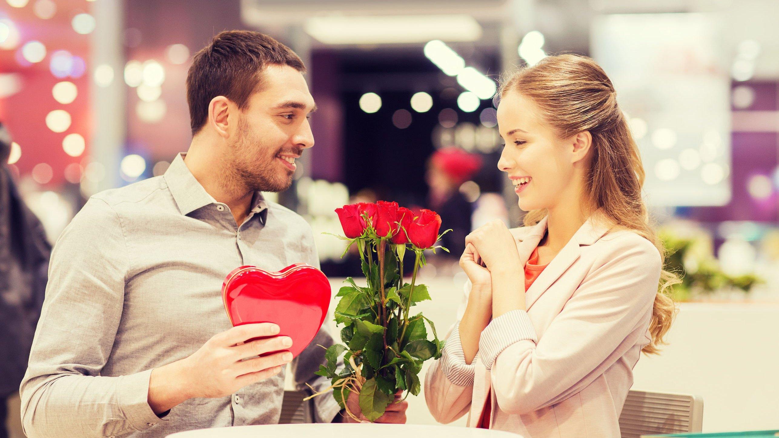 Homem entregando buquê de flores vermelhas para mulher