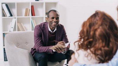Terapeuta, homem negro, sentado sorridente conversando com mulher e fazendo anotações