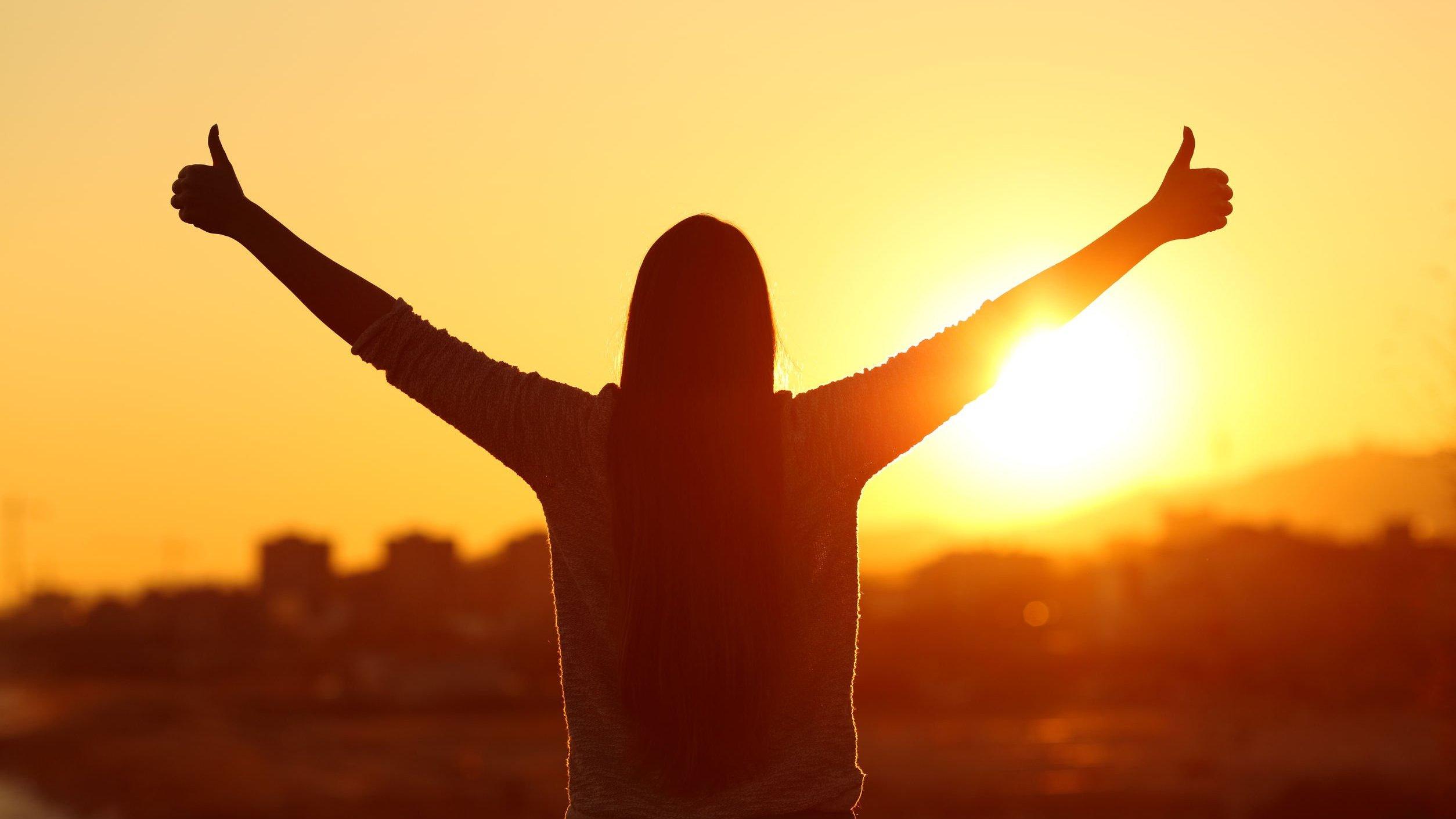 Silhueta de mulher com braços abertos para cima observando o pôr do sol