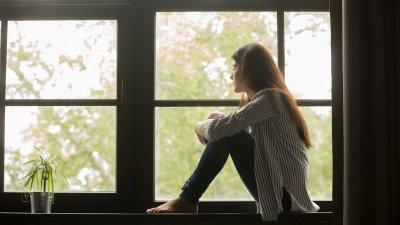Foto de mulher sentada olhando pela janela