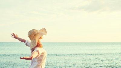 Foto de mulher em praia com braços abertos