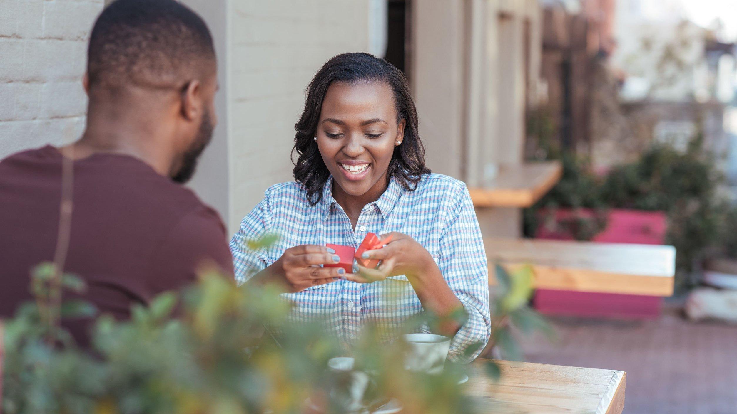 Homem e mulher sentados em um restaurante, enquanto ela abre uma caixa de presente e sorri.