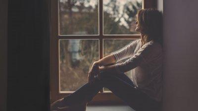 Mulher sentada na janela pensando