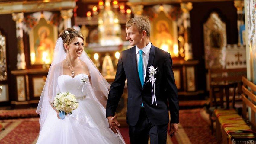 Mulher com vestido de noiva e homem com terno e gravata saindo de igreja de mãos dadas após seu casamento.