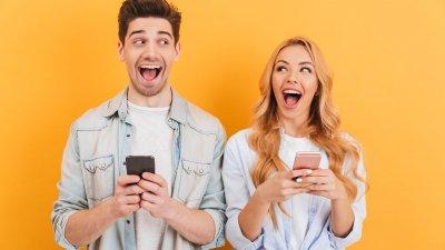 Homem e mulher lado a lado, rindo enquanto seguram seus smarthphones e olham um para o outro.
