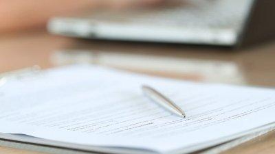Bloco de papéis com uma caneta prateada sobre. Ao fundo, uma mulher digita em um notebook.