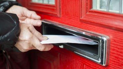 Pessoa colocando uma carta em abertura específica para tal em uma porta.