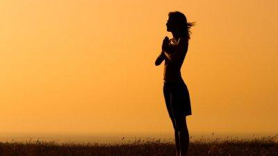 Mulher com mãos unidas em pé em campo
