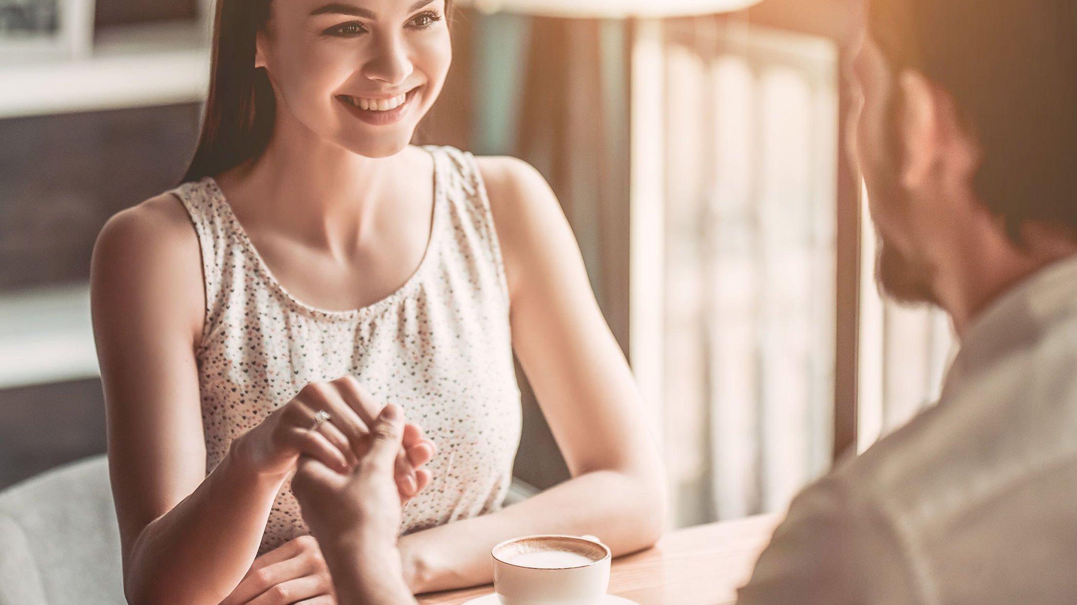 Mulher segurando a mão de homem enquanto ambos estão sentados em mesa de restaurante