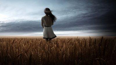 Menina de costas e cabelos ao vento em campo de trigo