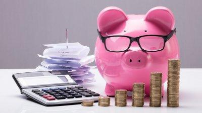 Cofre em formato de porquinho, moedas, calculadora