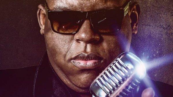 Homem usando óculos escuros em frente de microfone