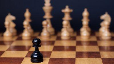 Peça de xadrez preta em tabuleiro com diversas outras peças beges