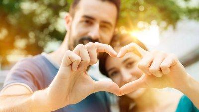 Mulher abraçando homem e ambos fazendo sinal de coração com as mãos juntas