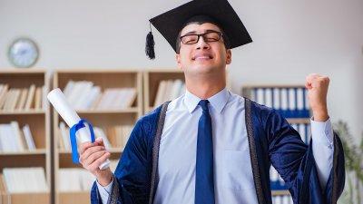 Homem se formando usando capelo e segurando diploma