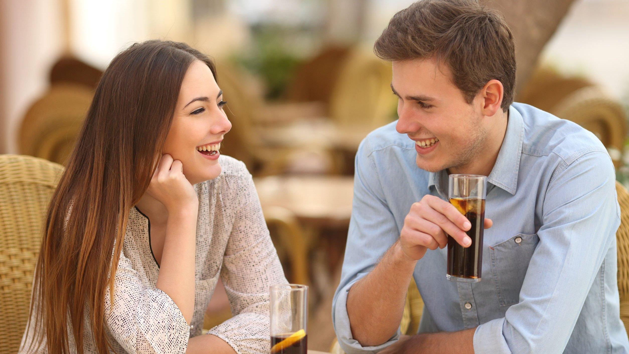 Homem e mulher conversando enquanto estão sentados em mesa de restaurante