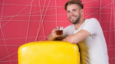 Homem sorrindo segurando copo com bebida