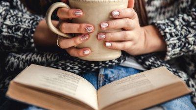 Pessoa lendo e tomando café
