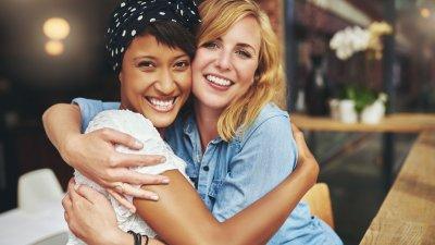 Amigas se abraçando e sorrindo