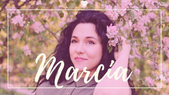 Mulher em jardim, com galho de flores atrás da orelha com o nome Márcia escrito em branco