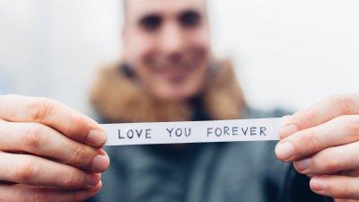 Homem segurando papel escrito amo você para sempre em inglês