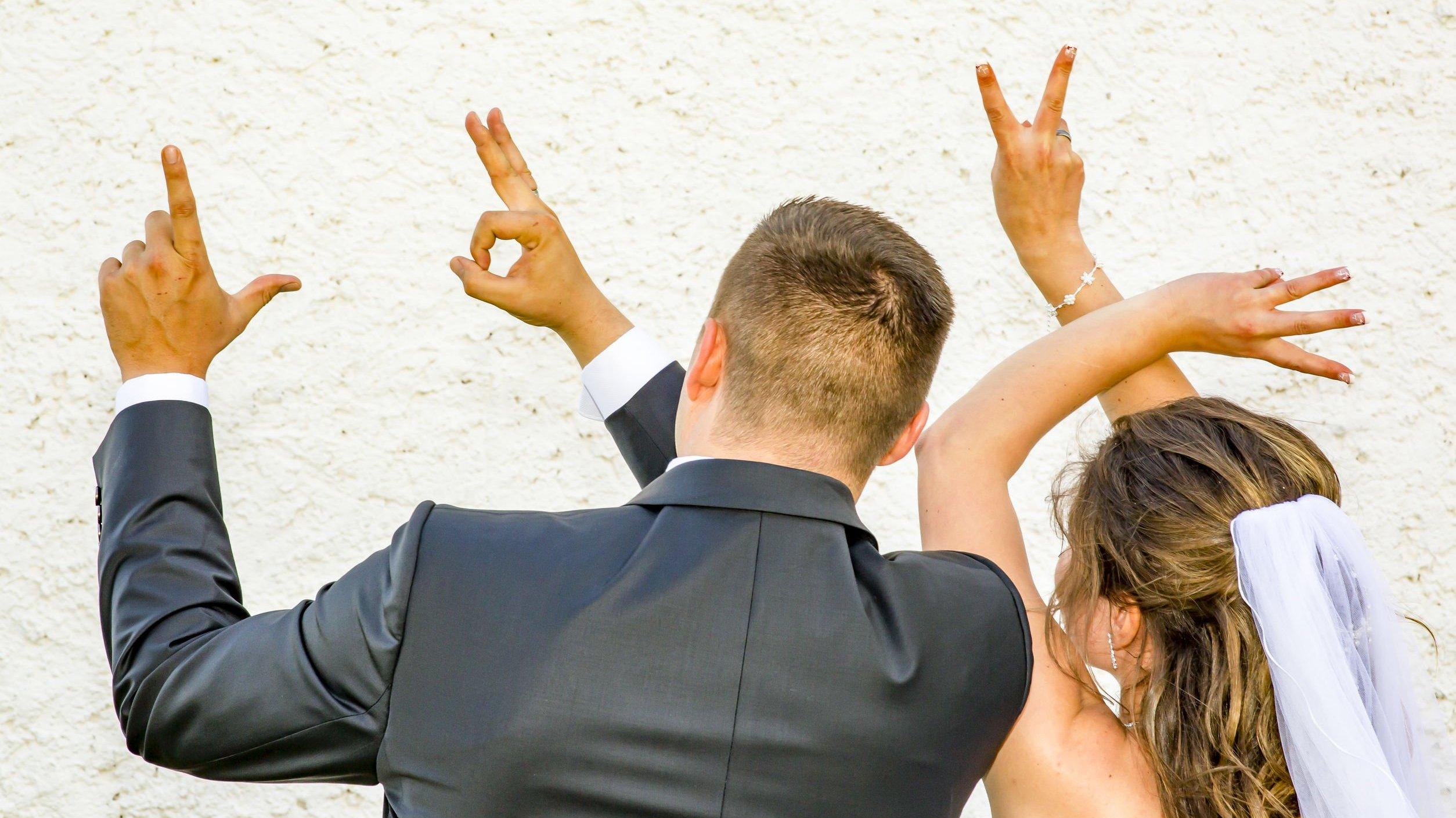 Casal formando a palavra love com as mãos