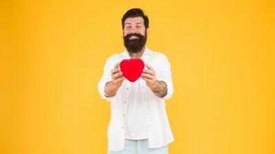 Homem sorrindo e segurando coração
