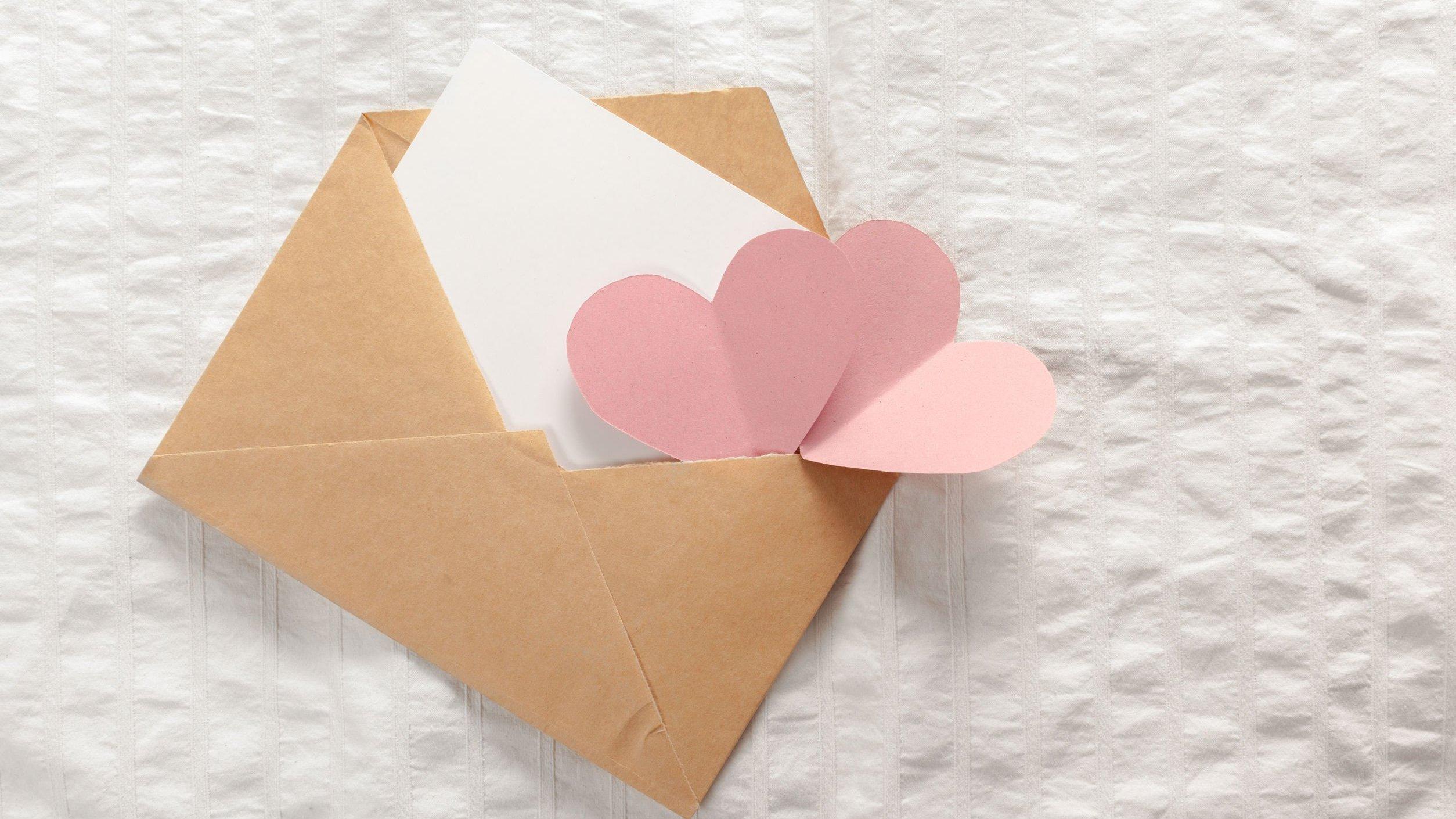 Envelope marrom aberto com carta branca e corações rosa claro saindo de dentro dele.