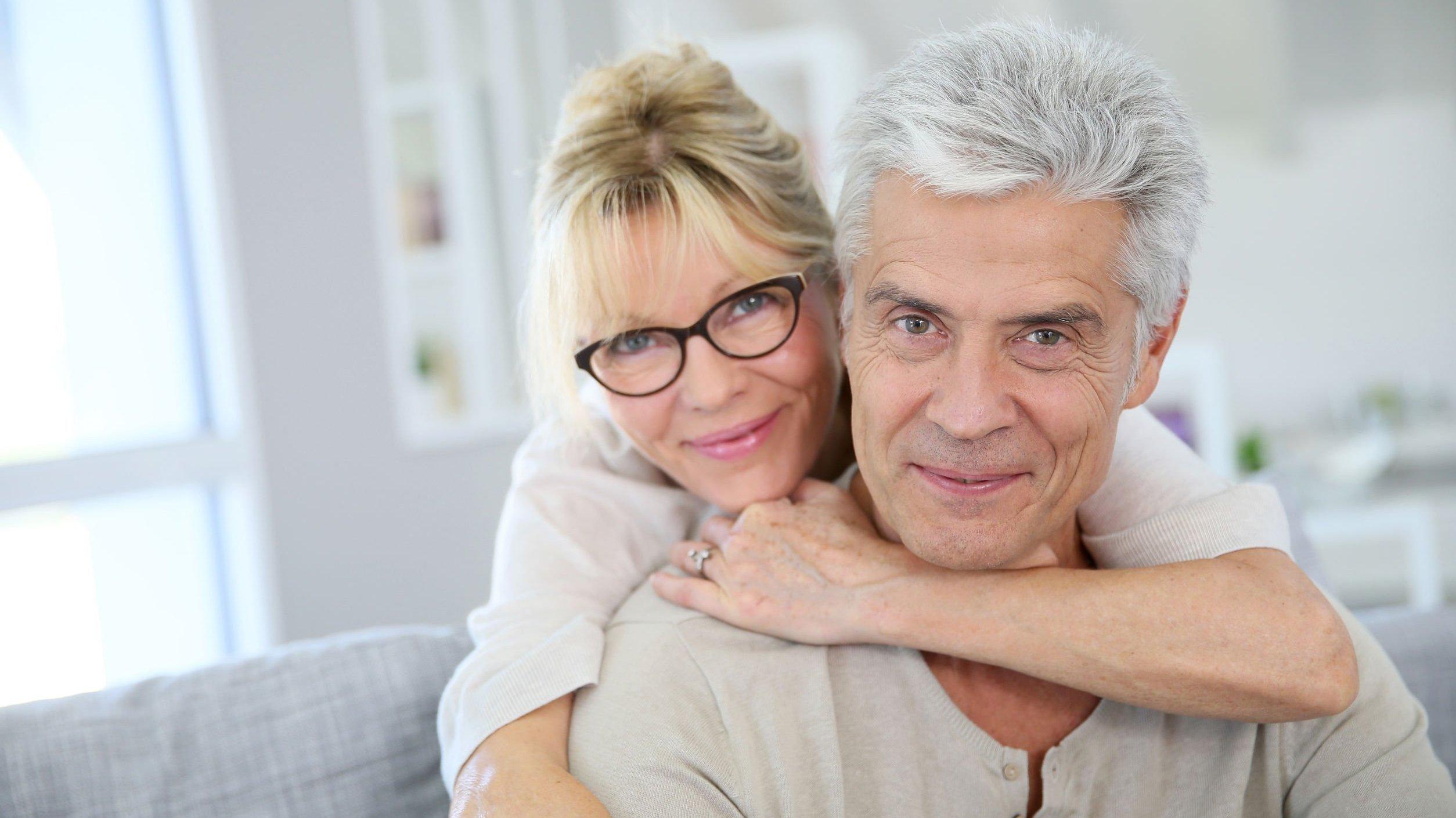 Casal de idosos sorrindo e se abraçando
