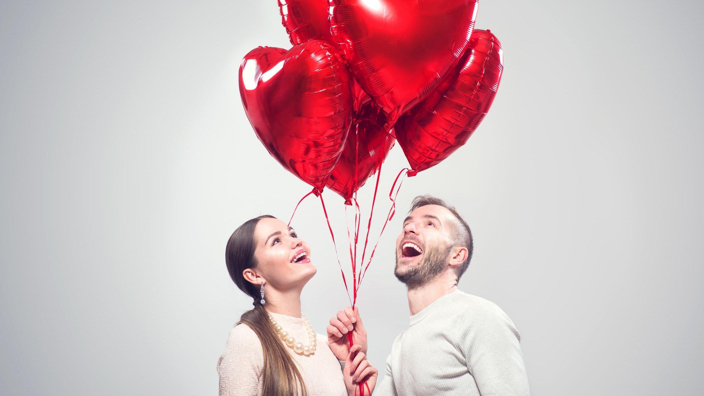 Homem e mulher seguram balões vermelhos em formato de coração