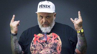 João Gordo fazendo sinal do rock com as duas mãos e com expressão séria no rosto