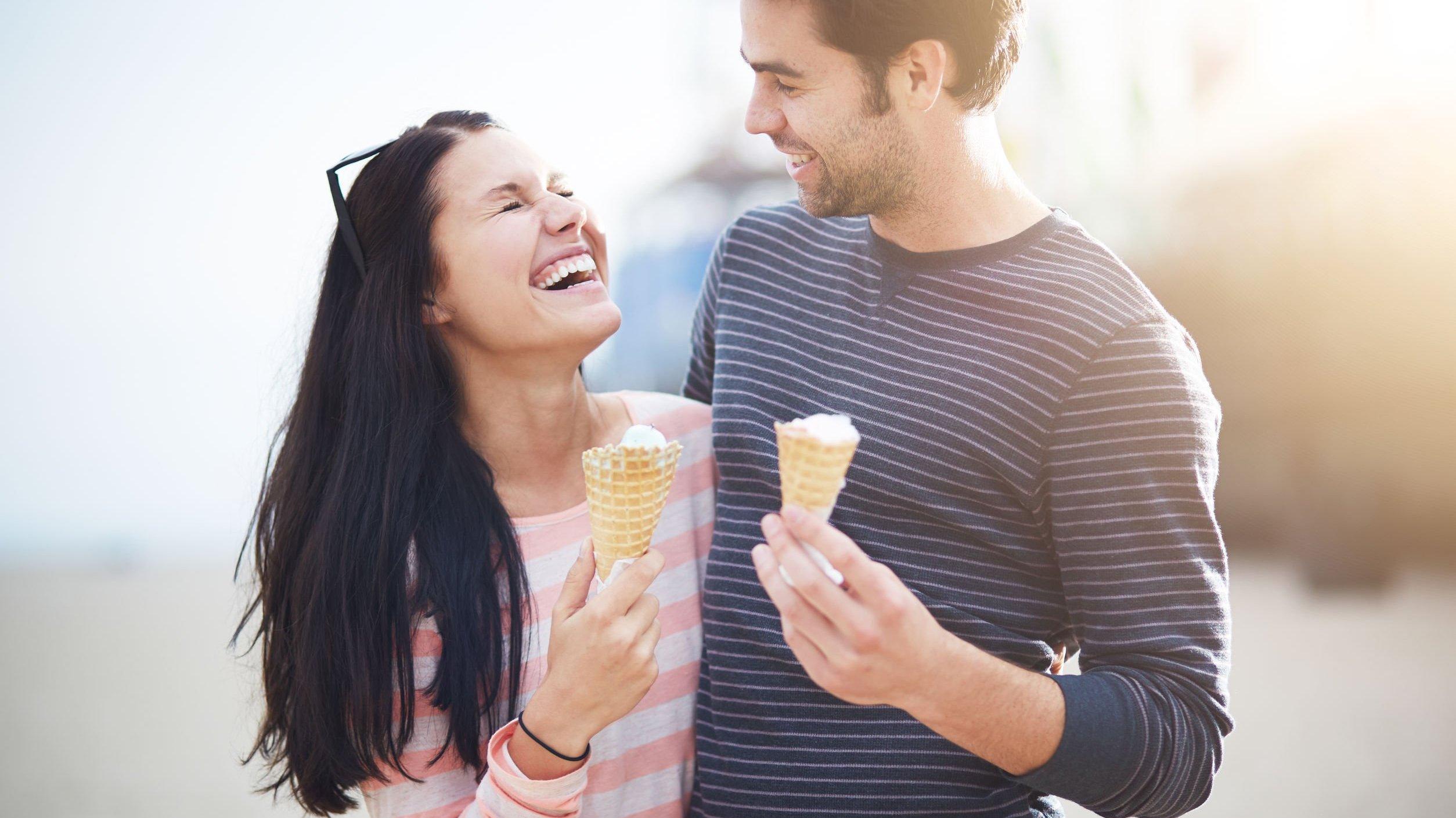Homem e mulher comendo sorvete e sorrindo